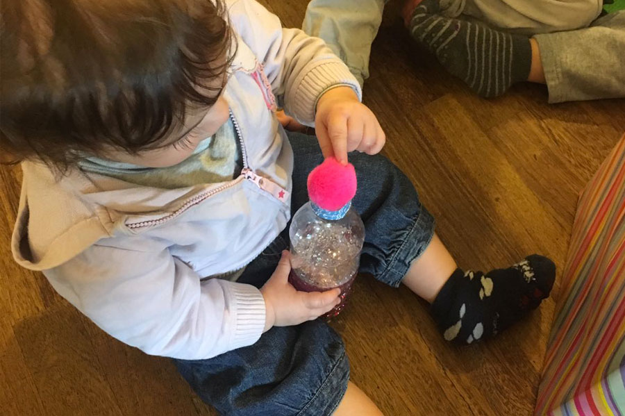 Bambino che gioca con una bottiglietta sensoriale - ZeroSei