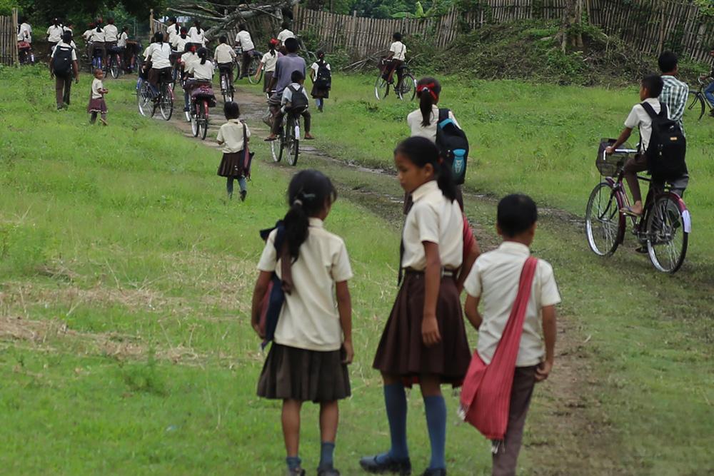 Bambini in bicicletta a scuola in India